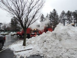 Giant scoops of snow are melted by special truck at the Americana in Manhasset