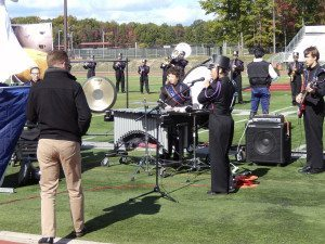 One of several USBands judges evaluates the band as seniors Christine Yoo (flute), Bryan Morrissey (baritone) and Jeffrey Chin (french horn) have featured solos in the band's second song of their Star Wars show at the NY state championship.