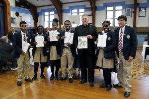 """Members of the St. Mary's High School Literary Club—""""Phoenix"""" proudly share their work with Fr. Robert Romeo, pastor of the Church of Saint Mary."""