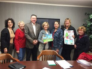 Manhasset Chamber of Commerce board members Suzanne Sokoloff, Katie Miller, CJ Coleman, Nancy Morris, Marion Stainkamp, Elizabeth Johnson and Diane Harragan holding up poster entries. Photo by Pat Grace