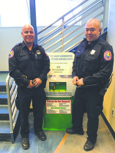 Nassau County Police Department POP Officers Rivera and Moy stand in front of the Third Precinct disposal box. Residents can dispose of unnecessary medications at any Nassau County Precinct or Police Center.